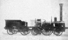 """Die """"Adler"""" war nicht nur die erste kommerziell erfolgreiche Dampflokomotive auf deutschen Boden, sie war auch die erste Dampflokomotive Cavembourgs. Als sie 1857 nach 22 Jahren Dienstzeit bei der Königlich privilegierte Ludwigs-Eisenbahn-Gesellschaft ausgemustert wurde, kaufte sie der Augsburger Geschäftsmann Ludwig August Riedinger (1809 -1879) samt Tender aber ohne Räder und anderen Verschleißteilen. Riedinger galt nicht nur als Menschenfreund, sondern auch als erster, der die Eisenbahn als Zeitverteib und Hobby für sich entdeckte. So gründete er eine Kranken– und Pensionskasse für die Mitarbeiter seiner """"Augsburger Mechanischen Baumwollspinnerei und Weberei"""", verhinderte mit seiner menschenfreundlichen Haltung Unruhen innerhalb seiner Arbeiterschaft im Revolutionsjahr 1848 und ließ die """"Adler"""" in den Werkstätten seiner Fabrik fahrtüchtig renovieren um """"mit ihr durch den Garten zu erfahren"""". Dazu kam es aber nie. Er lagerte sie nach der Instandsetzung in einem Schuppen, erklomm von Zeit zu Zeit den Führerstand und hielt sie bis ins Jahr 1865 in Schuss und fahrbereit. Als er von der, wie er glaubte, """"Befreiung"""" Cavembourgs durch die Franzosen hörte, der Vertreibung des letzten absolutistischen Königs und vom Bau der staatlichen Eisenbahn schenkte er die """"Adler"""" der neuen Cavembourgischen Eisenbahngesellschaft: """"...dem jungen Staate Cavembourg zum Wohle seiner freien Bürger auf ein höchstes zu unterstützen die Fesseln der Unterjochung zu sprengen und hinein zu erfahren in die Welten Länder!"""" wie es in der Schenkungsurkunde von Riedinger etwas überschwenglich formuliert wurde."""