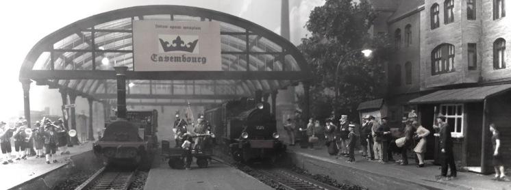 """Zusammen mit dem neuen Bahnhof Cavembourg/Stadt und der Eisenbahnstrecke nach Paris wurde auch die Verbindung zum Bahnhof Heinrichsburg fertiggestellt und eingeweiht. Die """"Adler"""" mit zwei Personenwagons erreichten den neuen Bahnhof um 11 Uhr 25. Eine Blaskapelle spielte und die zahlreichen Gäste begrüßten den Zug feierlich. Zu den Gästen gehörte neben Ministerpräsident Napf samt Frau auch der Erbauer und Chefingenieur der neuen Eisenbahnstrecke Georges-Eugène Baron Haussmann und der Industrielle Ludwig August Riedinger, der die Adler bekanntlich der cavembourgischen Eisenbahngesellschaft """"Société royale des chemins de fer cavembourgeoise SRCF"""" 1865 schenkte."""