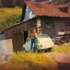 """Während des Cavemismus entstanden viele kleine und mittlere staatliche Manufakturen und Handwerksbetriebe, wie die """"Toholsche Hammerschmiede"""". Hier entwickelte der cavembourgische Schmied und Erfinder Magnus Ulrich Larzarius Tiberian Ignacius Tohol (1825 – 1900) unter anderem 1860 das erste nach ihm benannte mehrfunktionale Taschenmesser: Das """"Multitohol"""". Dieses Universalwerkzeug geriet nach dem Tod Tohols in Vergessenheit und wurde von Tom Lederman während einer Urlaubsreise durch Europa 1975, als er bei einer Autopanne an seinem Fiat 600 den Werkzeugkasten vermisste, in der Schmiede wieder entdeckt und später von ihm weiterentwickelt. Heute wird es weltweit unter dem Namen """"Lederman"""" oder """"Multitool"""" vermarktet. Dieses Foto zeigt Lederman nach dem er das Multitohol entdeckt hatte, es knipste seine Frau Mandy Lederman während der Autopanne 1975 vor der Toholschen Hammerschmiede,"""