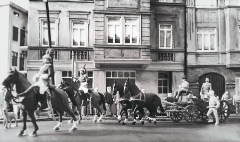 Unter dem Jubel der Bevölkerung fährt der König durch die Straßen der Hauptstadt. Kaum jemand bemerkt die schlechte Verfassung Heinrichs. Neben der Kutsche geht Karl Napf.